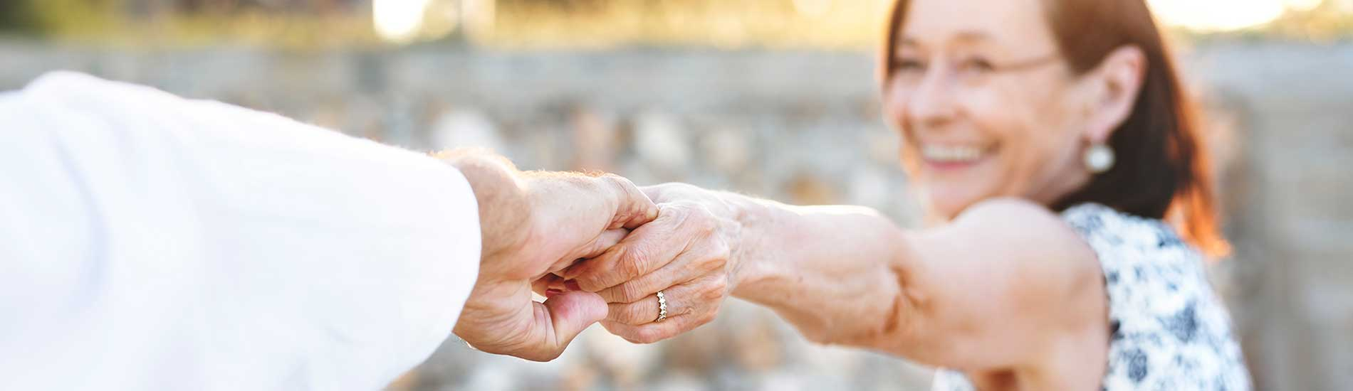 elderly woman holding husband's hand