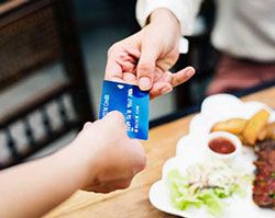 close shot of person passing credit card to another person