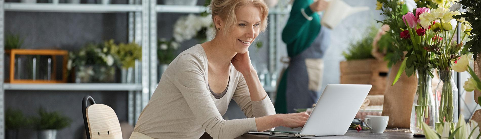 woman sitting at desk looking at laptop screen