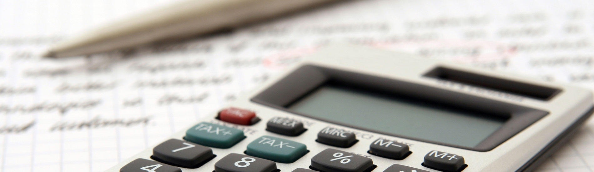 close-up of calculator and pen on graph paper
