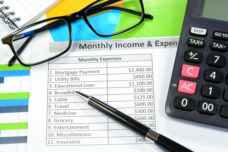 Paper with monthly expense list along with glasses and calculator