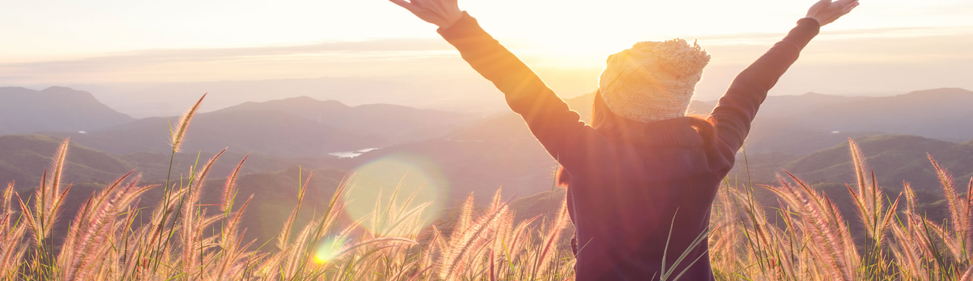Woman with outstretched hands to Sun coming over mountain range